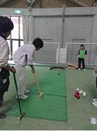 参加者のみなさんが、金づちの柄を長くしたような棒で、床に置いたりんご大のボールを打って転がしています。