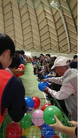 参加者の皆さんが並び、色とりどりの風船を隣の人に渡す速さを競っています。