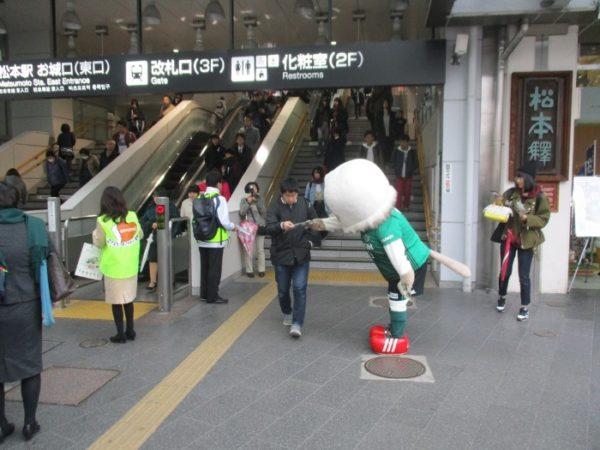 松本山雅のマスコットキャラクター『ガンズ君』が、松本駅の利用者の方にヘルプマークデザイン入りポケットティッシュを手渡しています。