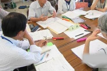 年齢も性別も様々な6人がテーブルを囲み、ノートを広げ、話し合っている写真です。