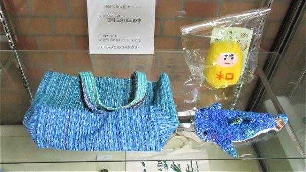 「明科ふきぼこの家」さんの展示品写真です。さをり織りバッグ、黄色いだるま、クジラのポーチなど。