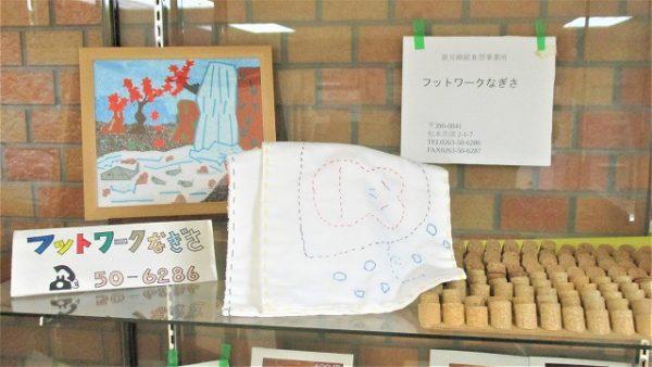 「フットワークなぎさ」さんの展示品写真です。刺し子のふきん、コルクのマッサージマット、紅葉と滝が描かれた風景画など。