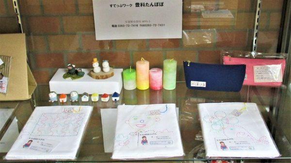 「豊科たんぽぽ」さんの展示品写真です。刺し子ふきん、帆布ペンケース、キャンドル、陶芸製品など。