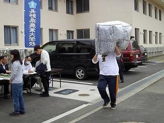 大きな荷物を運ぶ男子学生(本当は軽いんです。)